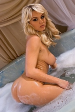 Bree Olson scoops a handful of bubble bath bubbles to lather up her naked chest
