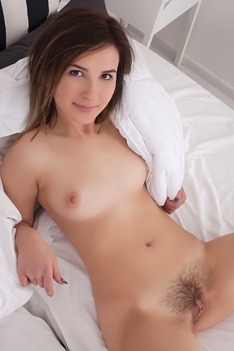 cute Ukrainian brunette lounges on her bed